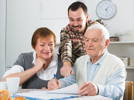 Elderly man and woman with employee of social department filled data form Stock Photo