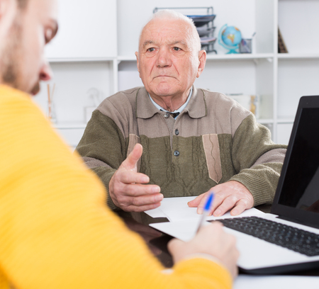 eldest: Old man and agent sign life and health insurance contract in office