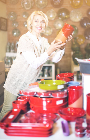 ware: Mature positive woman chooses ceramic ware in the cookware section at hypermarket