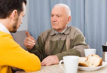 teaches: Aged father teaches and instructs his young son at table at home Stock Photo