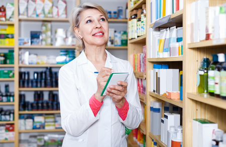 specialized job: Attractive woman seller writing down assortment of care products in shop
