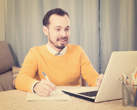 Young male student studying at online courses productively at home Stock Photo
