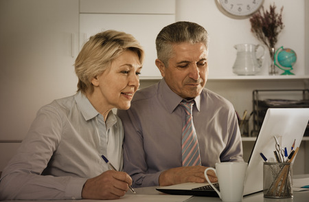 Mature employees working with documents together at computer at office