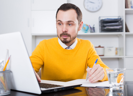 interviewed: Male student having a productive day at online courses at home Stock Photo
