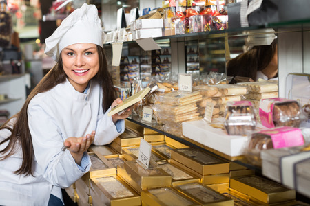 Young shopgirl posing with delicious chocolate and candies at display