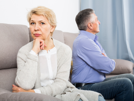 disappointed middle-aged couple quarreling at home with each other and take offense