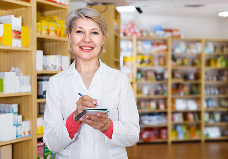 specialized job: Mature woman seller is checking assortment of care products in store.