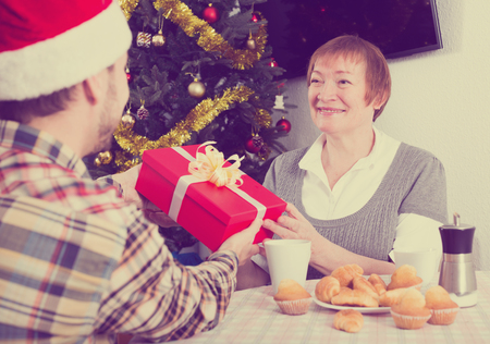 elderly mother and her son exchange holiday christmas gifts at festive table stock photo 77006781