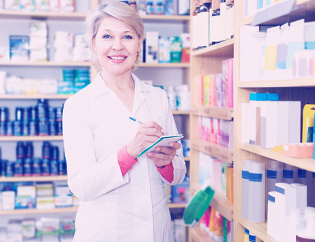 specialized job: Smiling woman seller writing down assortment of care products in shop