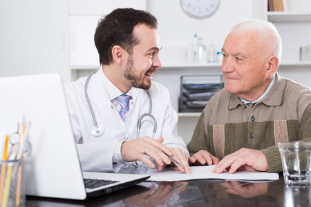 Old retired man consulting smiling man doctor in hospital