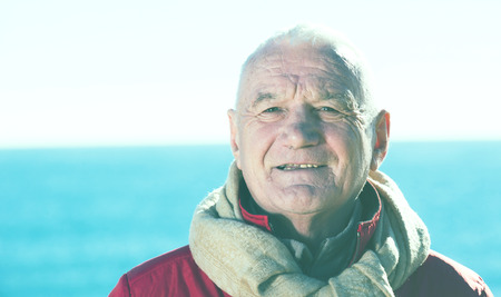 Aged man taking stroll alone on beach in cold season