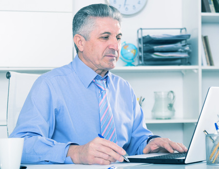 Mature lawyer preparing important documents on computer at his office Stock Photo