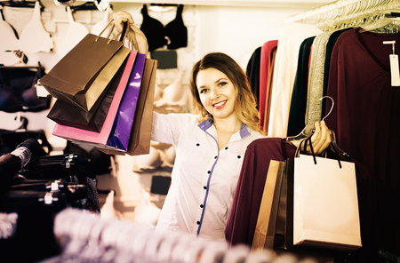 boasting: Woman is enjoying her purchases in wear shop.