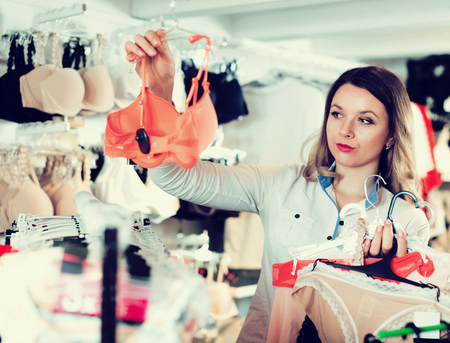 Smiling young woman customer choosing lingerie in underwear shop