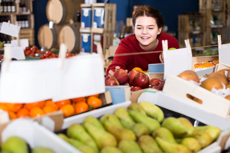 winesap apple: portrait of  positive young customer selecting apple in grocery