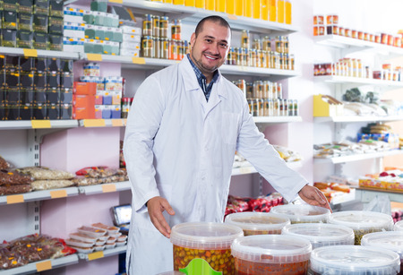 small articles: smiling  shop staff standing near containers with olives in flavoured brine