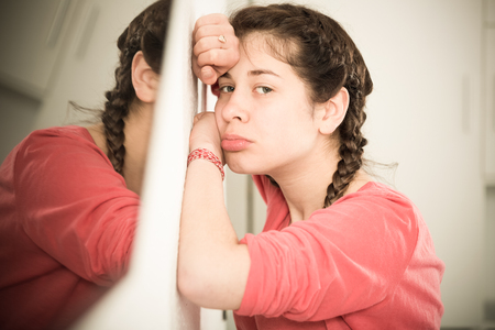 friendless: Young girl feeling distressed and lonely alone at home