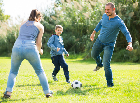 Mother, father and little boy playing football on field. Focus on man