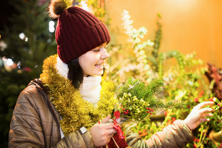 overspending: Young teen girl staying near counter with floral composition at Xmas fair Stock Photo