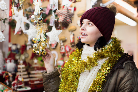 Happy young girl shopping at festive fair before Xmas