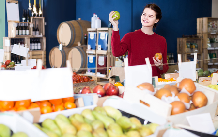 winesap apple: portrait of positive russian young customer selecting apple in grocery Stock Photo