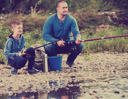 Happy adult man and boy spending time outdoors and fishing Stock Photo