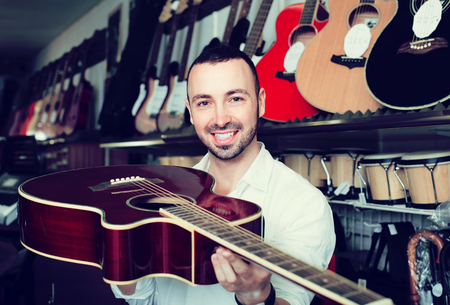 Young customer in white shirt selecting classical guitar at studio