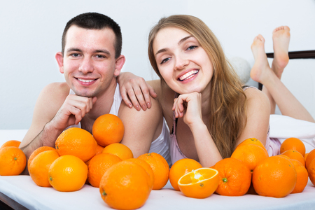 Young couple posing with ripe oranges in bed in home interior