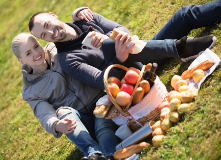 Young happy couple lounging in sunny spring day at picnic outdoors and smiling