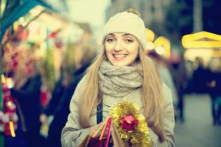 Portrait of positive cheerful  smiling woman at Christmas fair  in evening