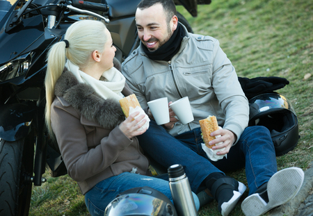 Portrait of young adults drinking tea and chatting near motorcycle