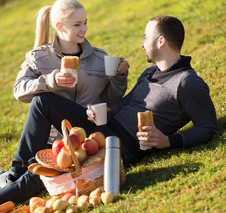 Young positive family couple lounging in sunny spring day at picnic outdoors. Focus on girl Stock Photo