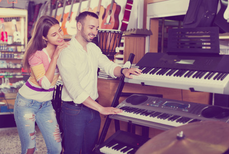 音楽シンセサイザーを選択する陽気なカップルの笑顔若い楽器店 写真素材 - 77079806