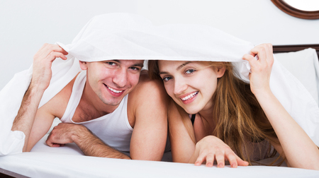 Young loving couple lounging in bed hiding under cover in bedroom