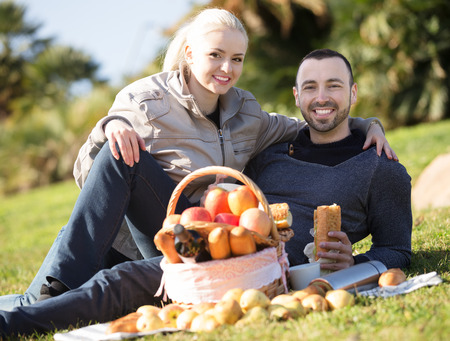 sandwitch: Young family couple lounging in sunny spring day at picnic outdoors and smiling. Focus on man