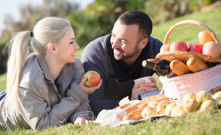 sandwitch: Smiling adult couple lounging in sunny spring day at picnic outdoors Stock Photo