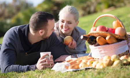 curare teneramente: Giovane coppia positiva oziare nella soleggiata giornata primaverile a pic-nic all'aperto