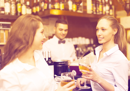 Two beautiful girls flirting with handsome barman Stock Photo