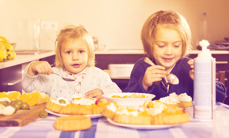Two  little sisters enjoying pastry with cream in kitchen