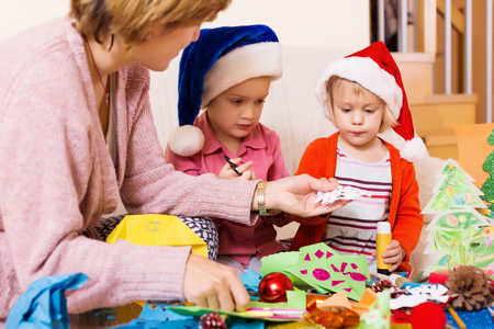 woman helping little girls to make decoration for Xmas  at home