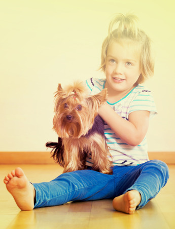 Happy child holding Yorkshire Terrier and smiling