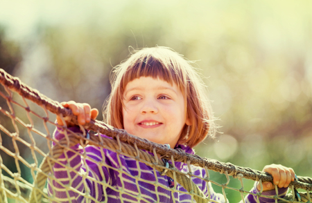 laughing baby girl climbing on ropes at playground area