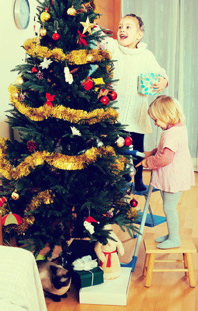 Little girls around three of five years old decorating a christmas tree