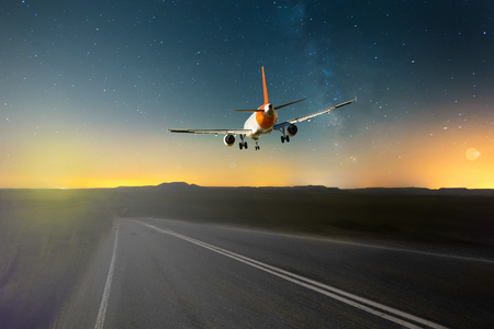 prespective: Airliner over highway in sunny day on mountain landscape background Stock Photo