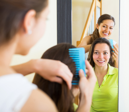 Smiling young women combing the hair in front of mirror Stock Photo