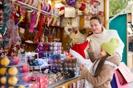 Little girl with 35-40 years old mom buying decorations for Xmas. Focus on girl Stock Photo