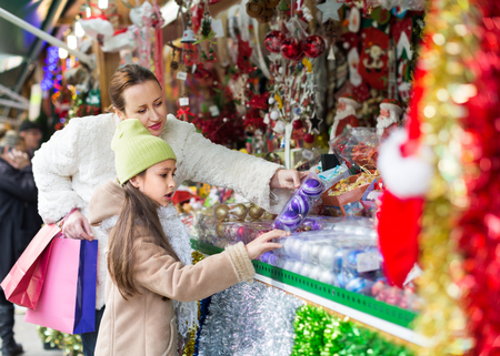 5s: Little girl with mom buying decorations for Xmas on market. Focus on woman