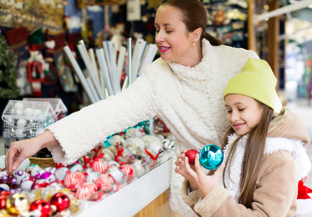 overspending: mother with happy daughte buying decorations for Xmas. Focus on woman Stock Photo