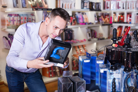 Young handsome man buying a sex toys at shop and smiling