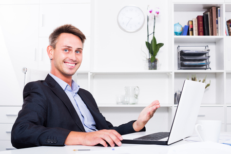 Cheerful man in formalwear sitting and working with computer at a company office
